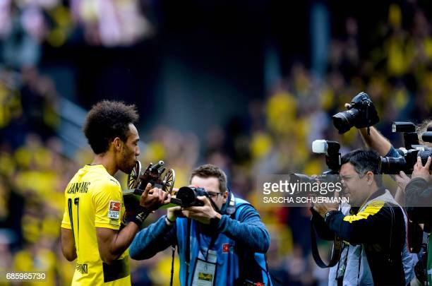 Dortmund's Gabonese forward PierreEmerick Aubameyang kisses the trophy for Bundesliga top scorer after the German first division football match...
