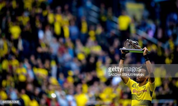 Dortmund's Gabonese forward PierreEmerick Aubameyang lifts the trophy as the Bundesliga's topscorer after the German first division football match...