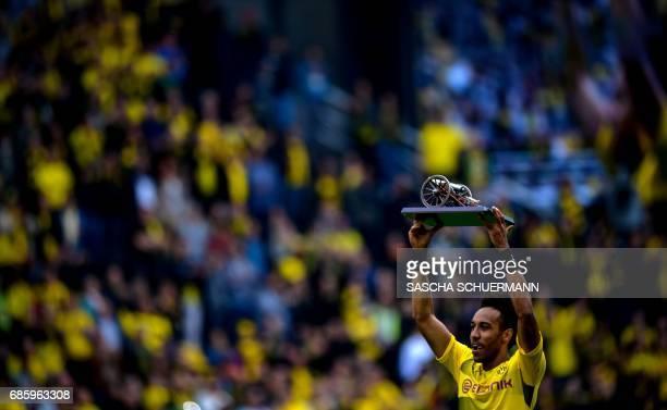 Dortmund's Gabonese forward PierreEmerick Aubameyang lifts the trophy as the Bundesliga's topscorer after the German first division football match...