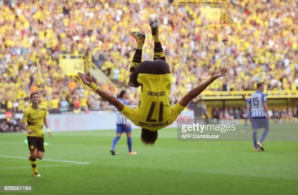 Dortmund's Gabonese forward PierreEmerick Aubameyang makes a somersault after scoring the first goal during the German First division Bundesliga...