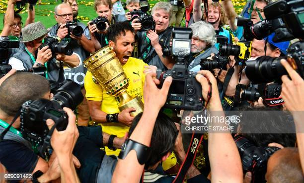 Dortmund's Gabonese forward PierreEmerick Aubameyang poses with the trophy for photographers after Dortmund won the German Cup final football match...