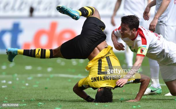 TOPSHOT Dortmund's Gabonese striker PierreEmerick Aubameyang falls beside of Augsburg's Dutch defender Paul Verhaegh during the German first division...