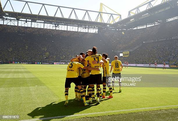 Dortmund's Gabonese striker PierreEmerick Aubameyang is congratulated by teammates after scoring the 10 during the German first division Bundesliga...