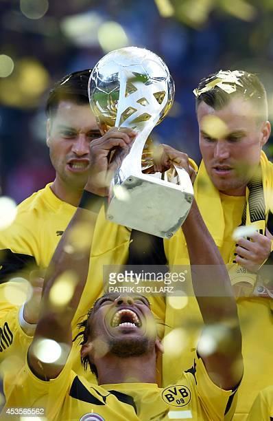 Dortmund's Gabonese striker PierreEmerick Aubameyang lifts up the trophy after the German Supercup football match Borussia Dortmund vs Bayern Munich...