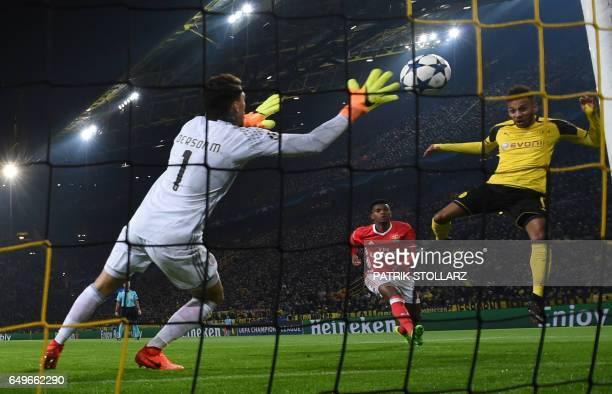 Dortmund's Gabonese striker PierreEmerick Aubameyang scores the opening goal past Benfica's Brazilian goalkeeper Ederson Moraes during the UEFA...