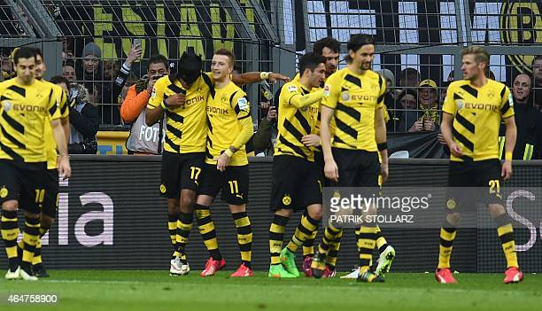 Dortmund's Gabonese striker PierreEmerick Aubameyang wears a mask as he celebrates his goal with Dortmund's striker Marco Reus and other teammates...