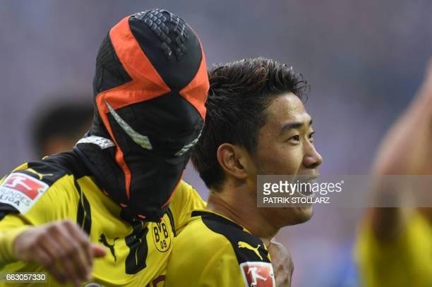 Dortmund's Gabonese striker PierreEmerick Aubameyang wears a mask as he celebrates with his teammate Dortmund's Japanese midfielder Shinji Kagawa...