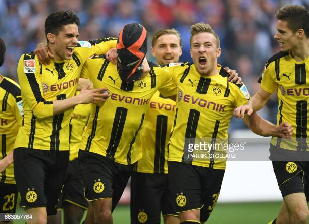 Dortmund's Gabonese striker PierreEmerick Aubameyang wears a mask as he celebrates with his teammates Dortmund's after scoring the 01 during the...