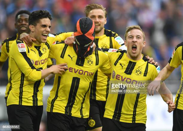 TOPSHOT Dortmund's Gabonese striker PierreEmerick Aubameyang wears a mask as he celebrates with his teammates Dortmund's after scoring the 01 during...