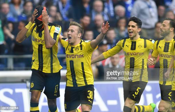 Dortmund's Gabonese striker PierreEmerick Aubameyang wears a mask as he celebrates with his teammates after scoring the 01 during the German first...
