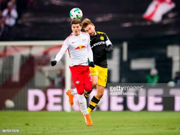 Dortmund's German defender Marcel Schmelzer and Leipzig's Austrian midfielder Marcel Sabitzer vie for the ball during the German first division...