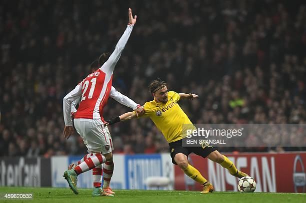 Dortmund's German defender Marcel Schmelzer tries to keep the ball in play under pressure from Arsenal's English midfielder Alex OxladeChamberlain...