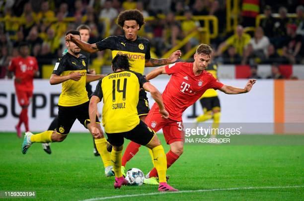 Dortmund's German defender Nico Schulz Dortmund's Belgian midfielder Axel Witsel and Munich's German defender Joshua Kimmich vie for the ball during...