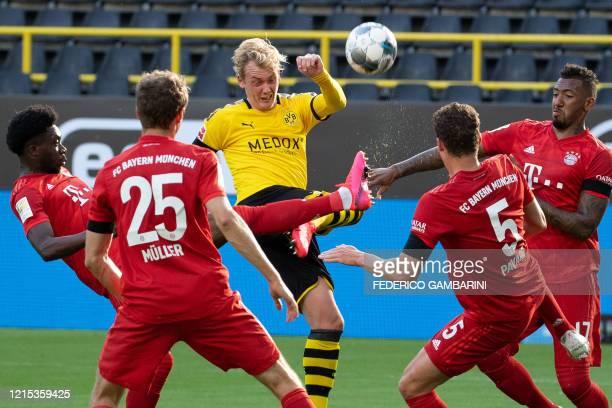 Dortmund's German forward Julian Brandt vies for the ball with Bayern Munich's Canadian midfielder Alphonso Davies Bayern Munich's German forward...