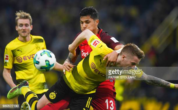 Dortmund's German forward Marco Reus and Frankfurt's Mexican defender Carlos Salcedo vie for the ball during the German first division Bundesliga...