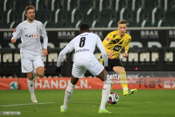 Dortmund's German forward Marco Reus and Moenchengladbach's Swiss midfielder Denis Zakaria vie for the ball during the German first division...