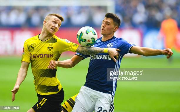 Dortmund's German forward Marco Reus and Schalke's Austrian midfielder Alessandro Schoepf vie for the ball during the German first division...