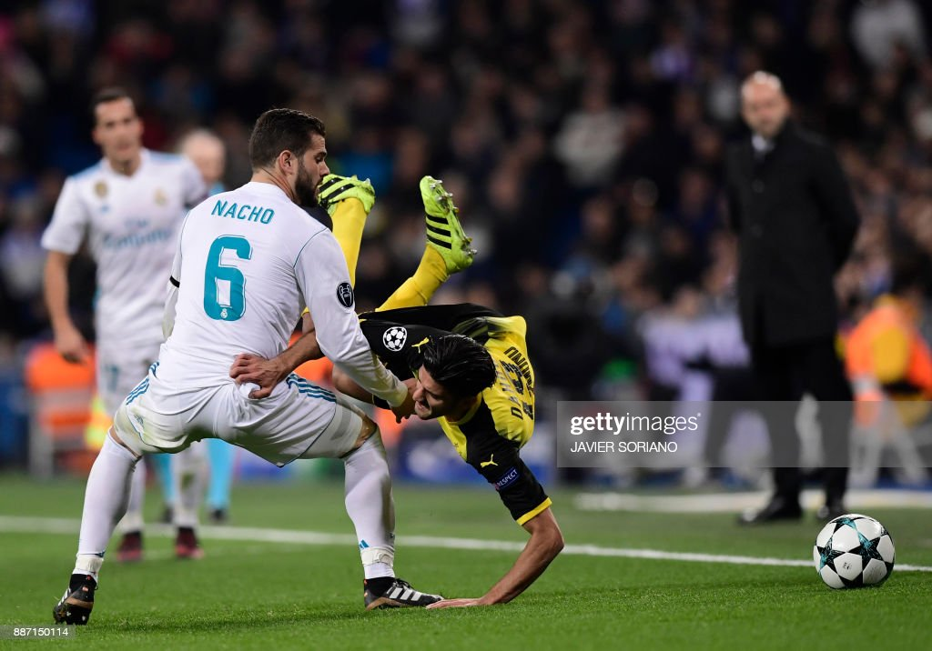 Dortmund's German midfielder Mahmoud Dahoud (R) vies with Real Madrid's Spanish defender Nacho Fernandez during the UEFA Champions League group H football match Real Madrid CF vs Borussia Dortmund at the Santiago Bernabeu stadium in Madrid on December 6, 2017. SORIANO / The erroneous mention[s] appearing in the metadata of this photo by JAVIER SORIANO has been modified in AFP systems in the following manner: [Dortmund's Portuguese defender Raphael Guerreiro] instead of [Dortmund's Portuguese defender Raphael Guerreiro]. Please immediately remove the erroneous mention[s] from all your online services and delete it (them) from your servers. If you have been authorized by AFP to distribute it (them) to third parties, please ensure that the same actions are carried out by them. Failure to promptly comply with these instructions will entail liability on your part for any continued or post notification usage. Therefore we thank you very much for all your attention and prompt action. We are sorry for the inconvenience this notification may cause and remain at your disposal for any further information you may require.