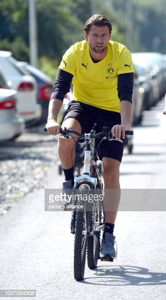 Dortmund's goalkeeper Roman Weidenfeller cycles to a morning training session at the training camp of Bundesliga soccer club Borussia Dortmund in Bad...