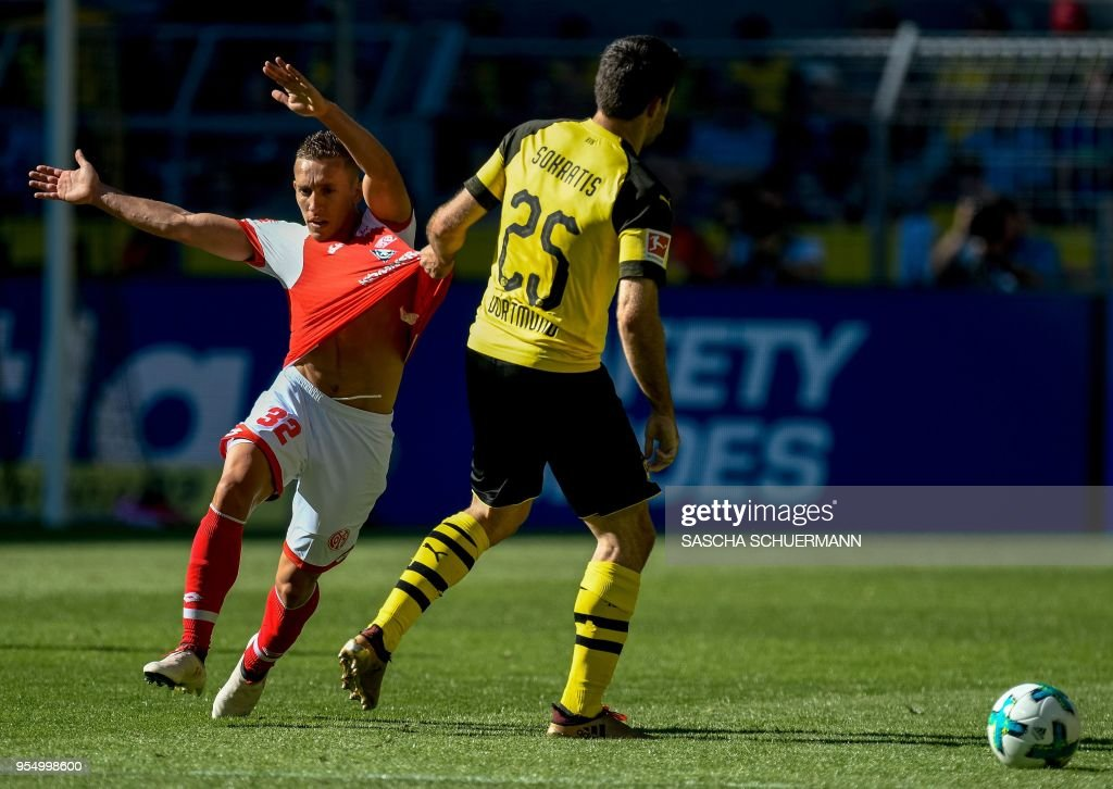 Dortmund's Greek defender Sokratis Papastathopoulos (R) pulls the shirt of Mainz's Argentinean forward Pablo De Blasis during the German first division Bundesliga football match Borussia Dortmund vs Mainz 05 in Dortmund, western Germany, on May 5, 2018. (Photo by SASCHA SCHUERMANN / AFP)