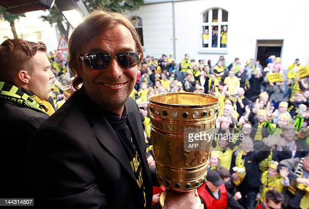 """Dortmund's head coach Juergen Klopp holds the German cup """" DFB Pokal """" during a parade through the streets of Dortmund, western Germany, on May 13,..."""