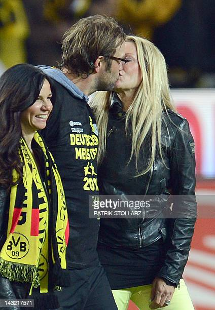 Dortmund's head coach Juergen Klopp kisses his wife Ulla while celebrating with Dortmund's manager's wife Jola Zorc after the German first division...