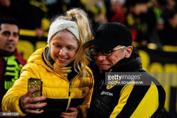Dortmund's head coach Peter Stoeger poses for a selfie photo with a fan prior to the German first division Bundesliga football match BVB Borussia...