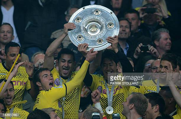 Dortmund's Japanese forward Shinji Kagawa Dortmund's midfielder Mario Goetze and Dortmund's midfielder Ilkay Guendogan lift the trophy after the...