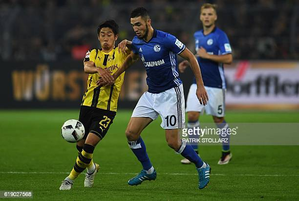 Dortmund's Japanese midfielder Shinji Kagawa and Schalke's defender Coke vie for the ball during the German first division Bundesliga football match...