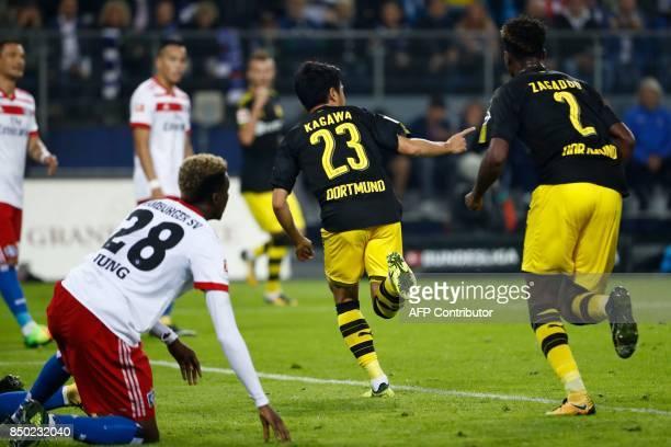 Dortmund's Japanese midfielder Shinji Kagawa celebrates scoring the opening goal with his teammates during the German first division Bundesliga...