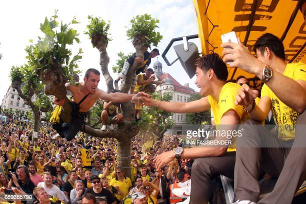Dortmund's Japanese midfielder Shinji Kagawa celebrates with fans as they arrive at Borsigplatz during celebrations after winning the German Cup...