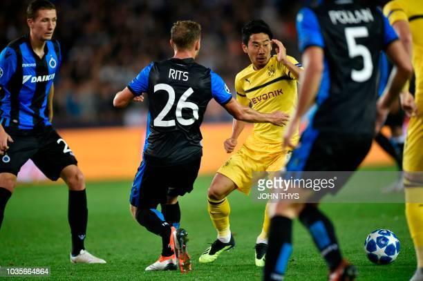 Dortmund's Japanese midfielder Shinji Kagawa cies with defenders during the UEFA Champions League Group C football match Club Brugge vs Borussia...