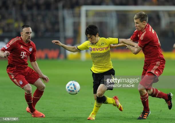 Dortmund's Japanese midfielder Shinji Kagawa is pressured by Munich's defender Holger Badstuber and Bayern Munich's French midfielder Franck Ribery...