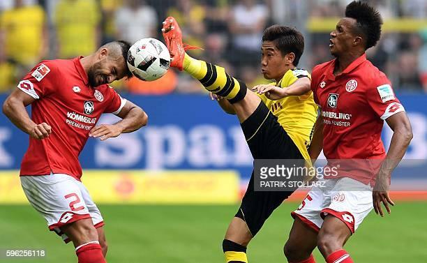 TOPSHOT Dortmund's Japanese midfielder Shinji Kagawa vies for the ball with Mainz' Italian defender Giulio Donati and Mainz' French midfielder Jean...