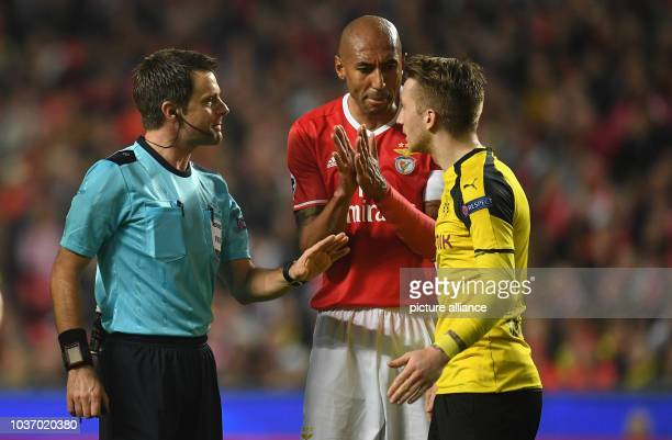 Dortmund's Marco Reus is involved in a discussion with the referee Nicola Rizzoli from Italy and Benfica's Lusiao during the Champions League round...