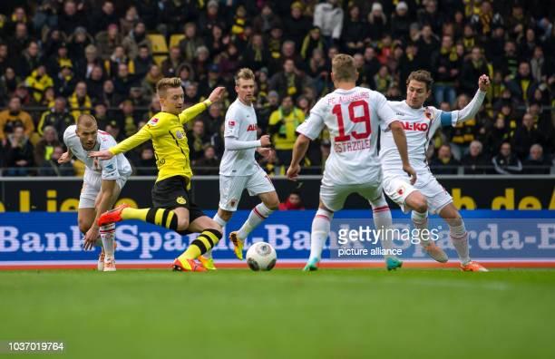 Dortmund's Marco Reus vies for the ball with Augsburg's Ragnar Klavan Paul Verhaegh and Matthias Ostrzolek during the Bundesliga soccer match between...