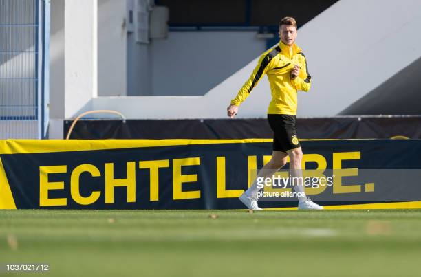 """Dortmund's Marco Reus walks by an advertising banner reading """"Echte Liebe"""" during training at the Borussia Dortmund training camp in Marbella, Spain,..."""