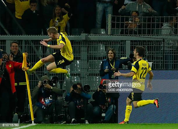 TOPSHOT Dortmund's midfielder Andre Schuerrle reacts after scoring during the UEFA Champions League first leg football match between Borussia...