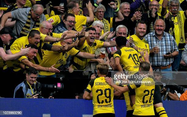 Dortmund's midfielder Axel Witsel celebrates with supporters and teammates after he scored his team's third goal during the German first division...