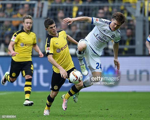 Dortmund's midfielder Christian Pulisic and Hamburg's Japanese defender Gotoku Sakai vie for the ball during the German Bundesliga first division...