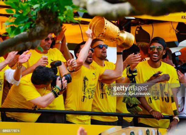 Dortmund's midfielder Gonzalo Castro holds up the trophy as Borussia Dortmund players arrive at Borsigplatz during celebrations after winning the...