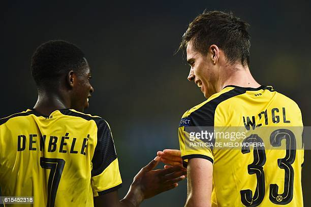 Dortmund's midfielder Julian Weigl celebrates with his teammate Dortmund's French forward Ousmane Dembele after scoring during the UEFA Champions...