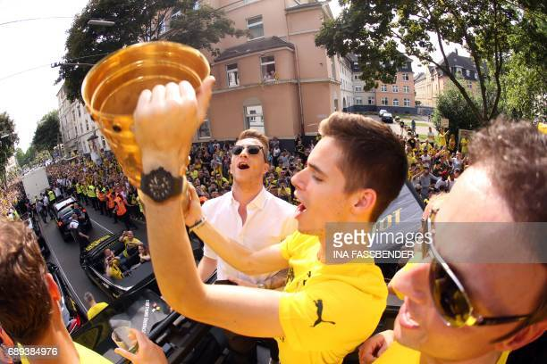 Dortmund's midfielder Julian Weigl raises the trophy as they arrive at Borsigplatz during celebrations after winning the German Cup final in Dortmund...