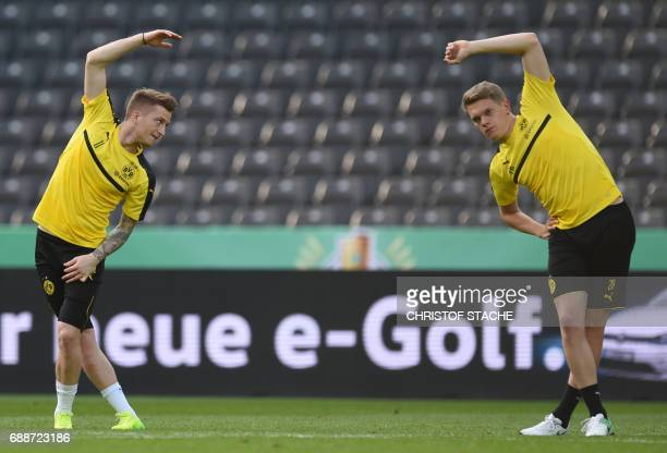 Dortmund's midfielder Marco Reus and Dortmund's defender Matthias Ginter stretch during a training session on the eve of the German Cup football...