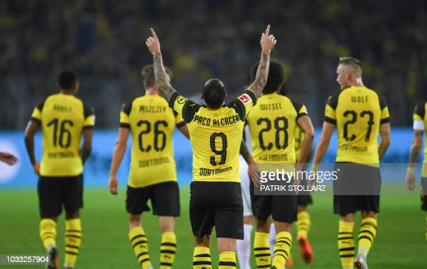 Dortmund's midfielder Paco Alacer celebrates with his teammates after scoring during the German first division Bundesliga football match Borussia...