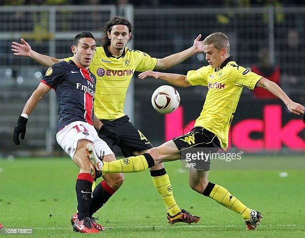 Dortmund's midfielder Sven Bender and Dortmund's US defender Neven Subotic vie for the ball with Paris' Turkish striker Mevluet Erdinc during the...
