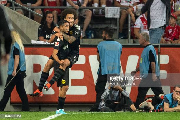 Dortmund's Moroccan defender Achraf Hakimi celebrate scoring the 12 goal with his teammate Belgian midfielder Axel Witsel during the German first...
