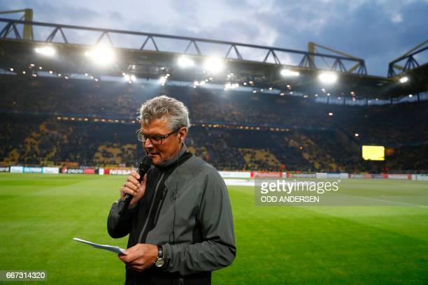 Dortmund's Norbert Dickel announces the postponementof the match after the team bus of Borussia Dortmund had some windows broken by an explosion some...