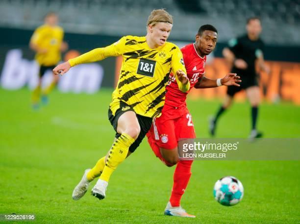 Dortmund's Norwegian forward Erling Braut Haaland and Bayern Munich's Austrian defender David Alaba vie for the ball during the German first division...