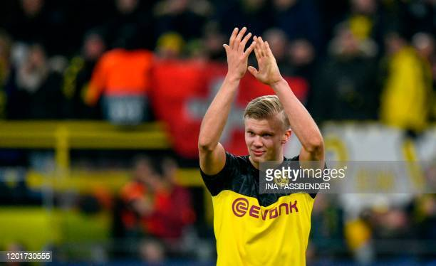 Dortmund's Norwegian forward Erling Braut Haaland applauds after the UEFA Champions League Last 16 firstleg football match BVB Borussia Dortmund v...